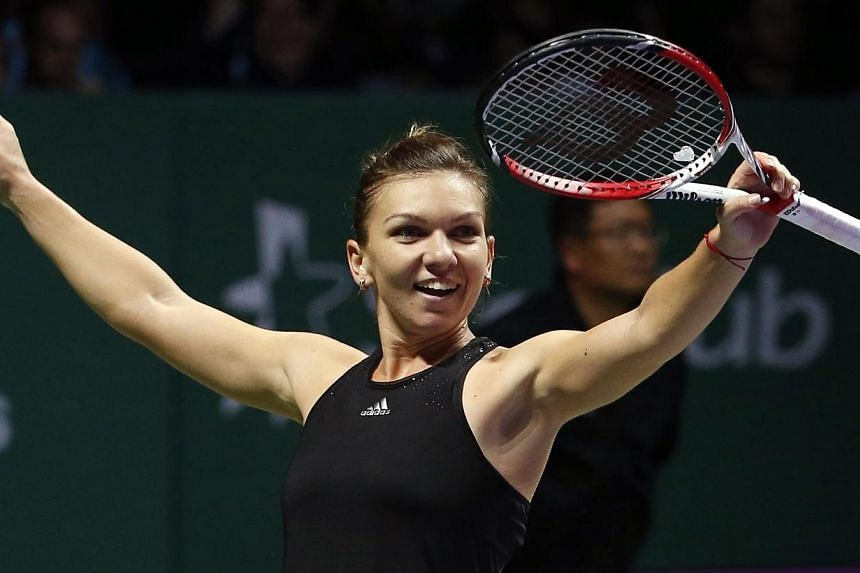 Simona Halep of Romania celebrates her win over Serena Williams of the US during their WTA Finals singles tennis match at the Singapore Indoor Stadium on Oct 22, 2014. -- PHOTO: REUTERS
