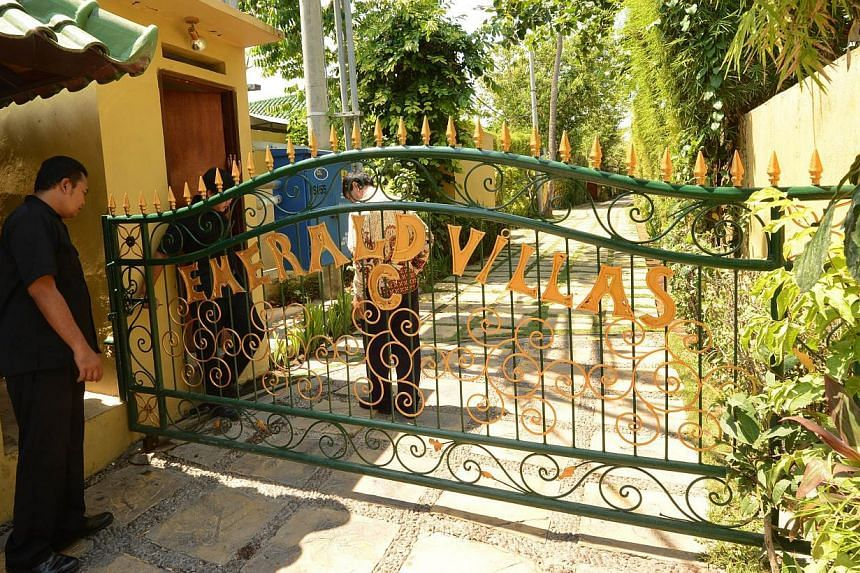 Security guards stand at the front gate of Emerald villas in Sanur on Bali island on Oct 22, 2014. -- PHOTO: AFP