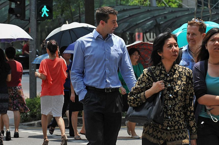 Lunchtime crowd and expats crossing Robinson Road in the CBD area on 2011. -- PHOTO: ST FILE
