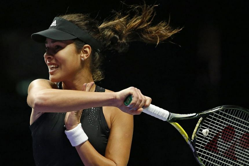 Ana Ivanovic of Serbia hits a return to Eugenie Bouchard of Canada during their WTA Finals singles tennis match at the Singapore Indoor Stadium on Oct 22, 2014.-- PHOTO: REUTERS