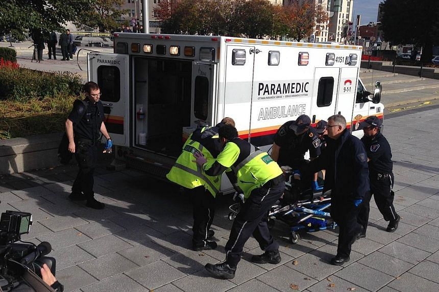 Police and paramedics transport a wounded Canadian soldier on Oct 22, 2014 in Ottawa, Ontario.Canadian police backed by armored vehicles surrounded parliament in Ottawa on Wednesday after a soldier was shot while guarding a nearby monument. --