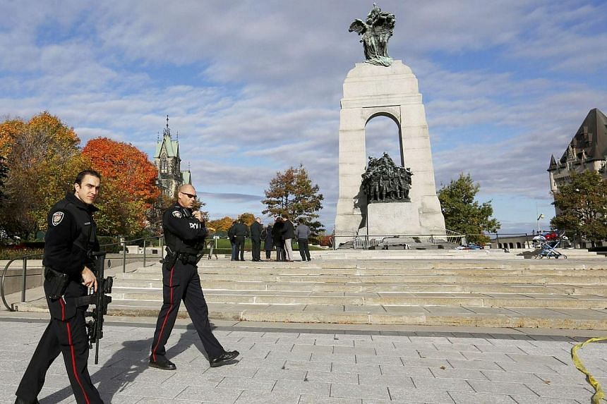 Police officers patrol alongside the Canadian War Memorial following a shooting incident in Ottawa on Oct 22, 2014. -- PHOTO: REUTERS