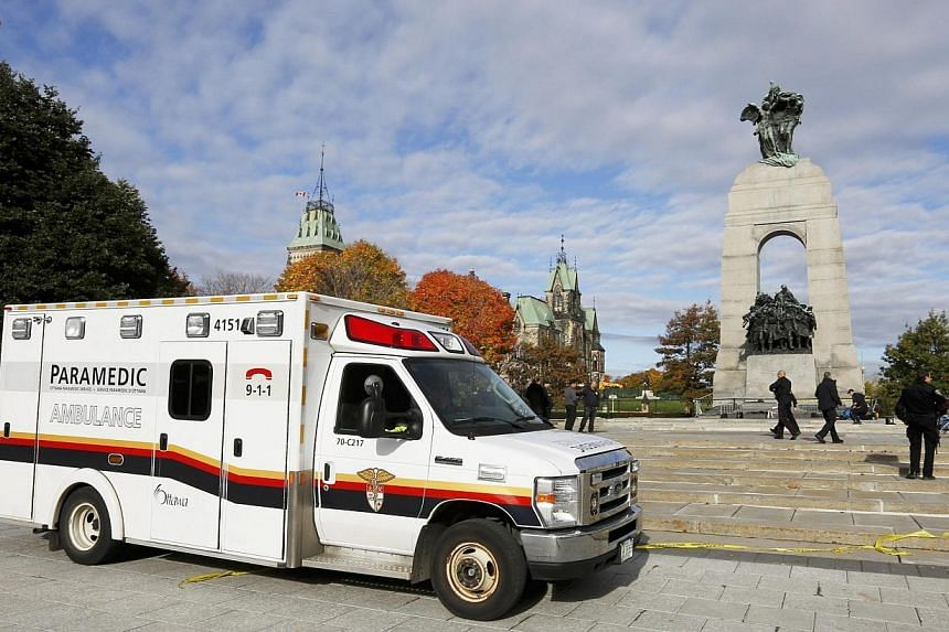 An ambulance is pictured alongside the Canadian War Memorial following a shooting incident in Ottawa on Oct 22, 2014. -- PHOTO: REUTERS