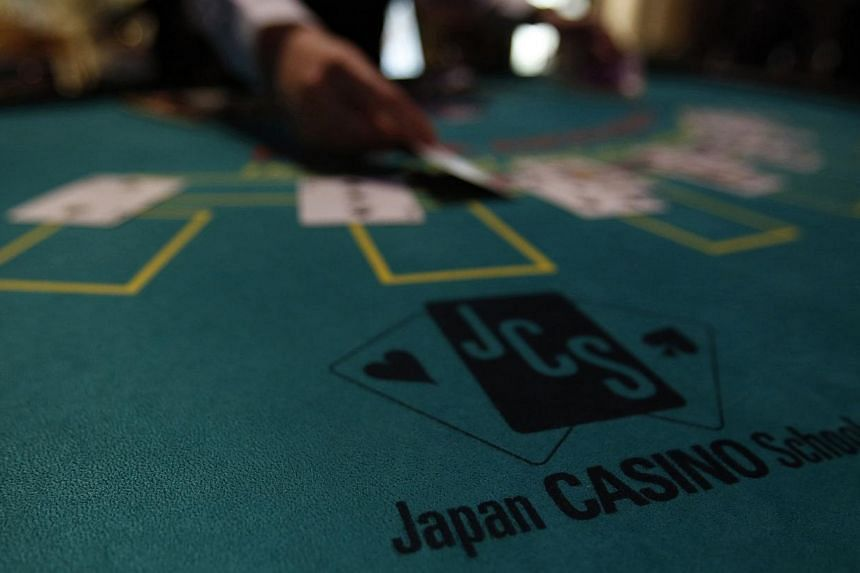A logo of Japan casino school is seen as a dealer puts cards on a mock black jack casino table during a photo opportunity at an international tourism promotion symposium in Tokyo on Sept 28, 2013.Japan's pro-casino lawmakers have given up debat