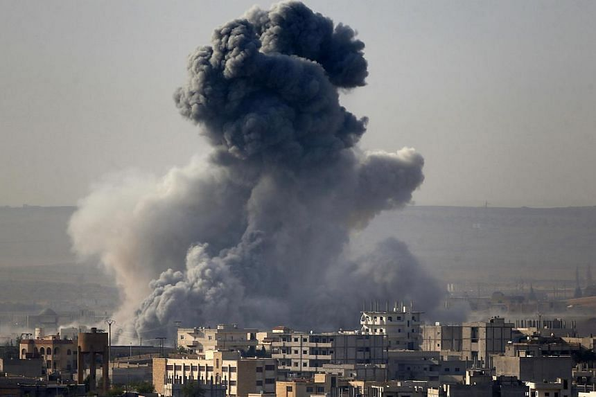 Smoke rises from the Syrian town of Kobani, seen from near the Mursitpinar border crossing on the Turkish-Syrian border in the southeastern town of Suruc in Sanliurfa province on Oct 14, 2014. -- PHOTO: REUTERS