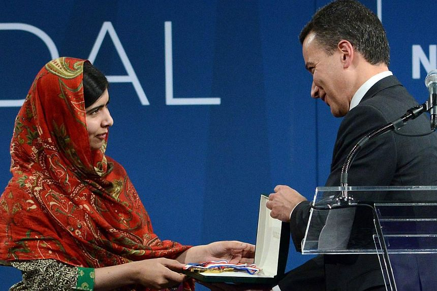 Pakistani activist Malala Yousafzai (left), 17-years-old, receives the 2014 Liberty Medal from Jeffrey Rosen, President and CEO of the National Constitution Center at the National Constitution Center in Philadelphia, Pennsylvaniaon Oct 21, 2014