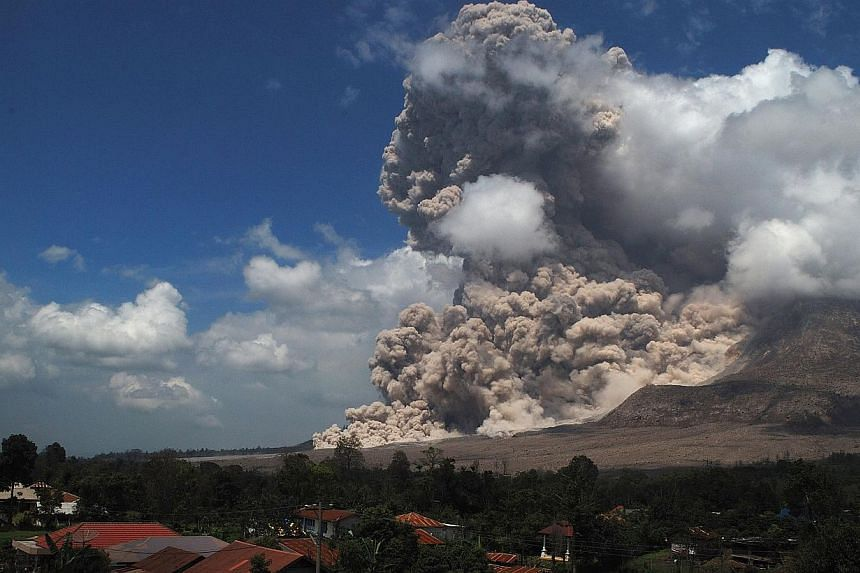 Super heated giant ash cloud spew from the crater of Mount Sinabung volcano threatening villages during an eruption on Oct 17, 2014 as seen from Simpang Empat district on Sumatra island. -- PHOTO: AFP