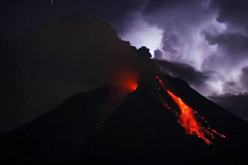 This long exposure photograph taken before dawn on Oct 18, 2014 shows super heated lava and giant ash clouds spewing from the crater of Mount Sinabung volcano threatening villages during an eruption as seen from Karo district on Sumatra island. -- PH
