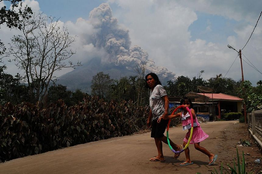 In this photograph taken on Oct 16, 2014, a woman and a child is seen in a village while Mount Sinabung volcano erupts in the background as seen from Karo district on Sumatra island. -- PHOTO: AFP