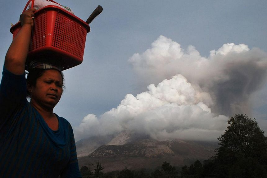 A woman carrying belongings flees from the eruption of Mount Sinabung volcano (background) seen from Karo district on Sumatra island on Oct 14, 2014. -- PHOTO: AFP