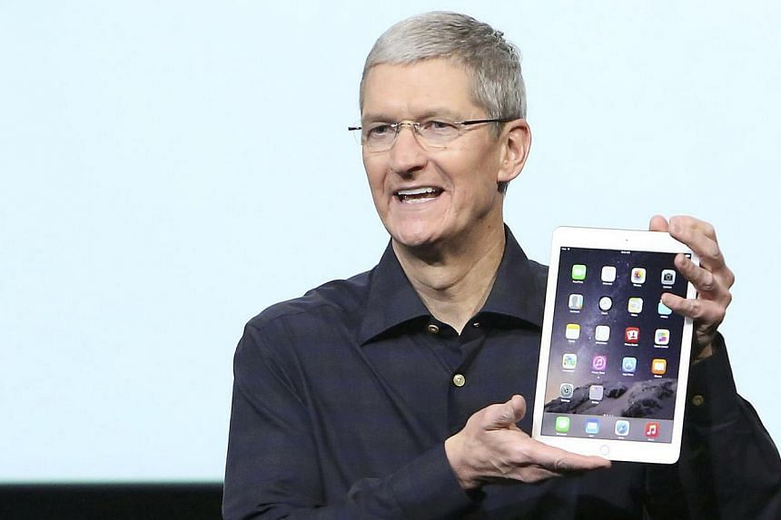Apple CEO Tim Cook holds an iPad during a presentation at Apple headquarters in Cupertino, California. -- PHOTO: REUTERS