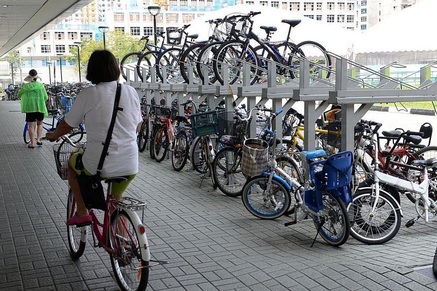 A woman cycling past the bike racks outside Seng Kang MRT station on August 21, 2014. -- PHOTO: ST FILE