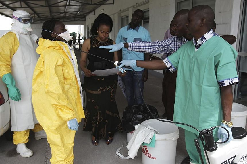 A health worker sprays a colleague with disinfectant during a training session for Congolese health workers to deal with Ebola virus in Kinshasa on Oct 21, 2014. -- PHOTO: REUTERS