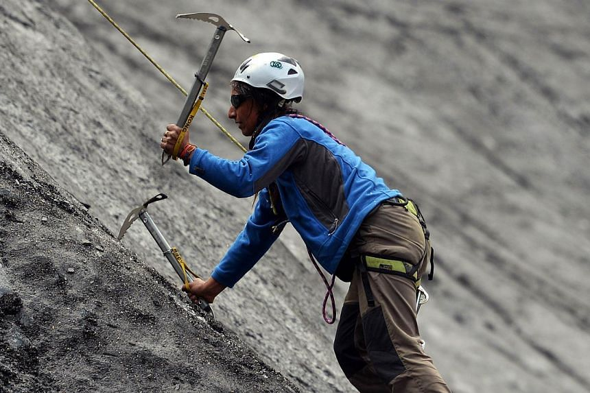 In this photograph taken on August 4, 2014, a Pakistani student from the Shimshal Mountaineering School uses ice axes to climb a slope on a glacier near the Shimshal village in the northern Hunza valley. Breaking taboos and pursuing jobs traditionall