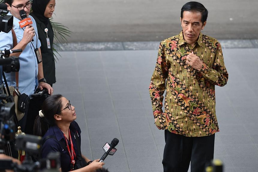 Indonesian President Joko Widodo (right) walks past the journalists outside the Palace in Jakarta on Oct 21, 2014. -- PHOTO: AFP