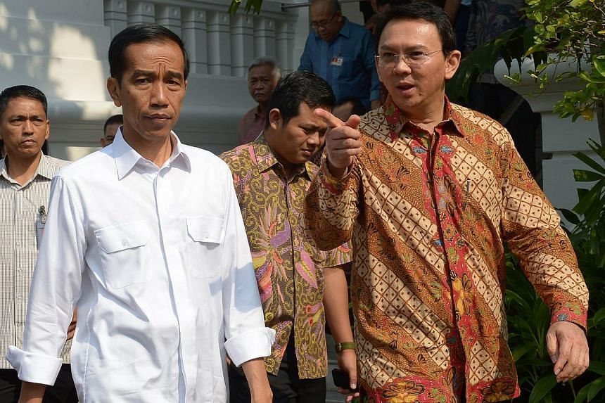 Indonesian President Joko Widodo (left) walks next to acting Jakarta governor Basuki Tjahaja Purnama at the presidential palace in Jakarta on October 22, 2014. Political opposition to him in Parliament is already taking on new shapes. This is one of