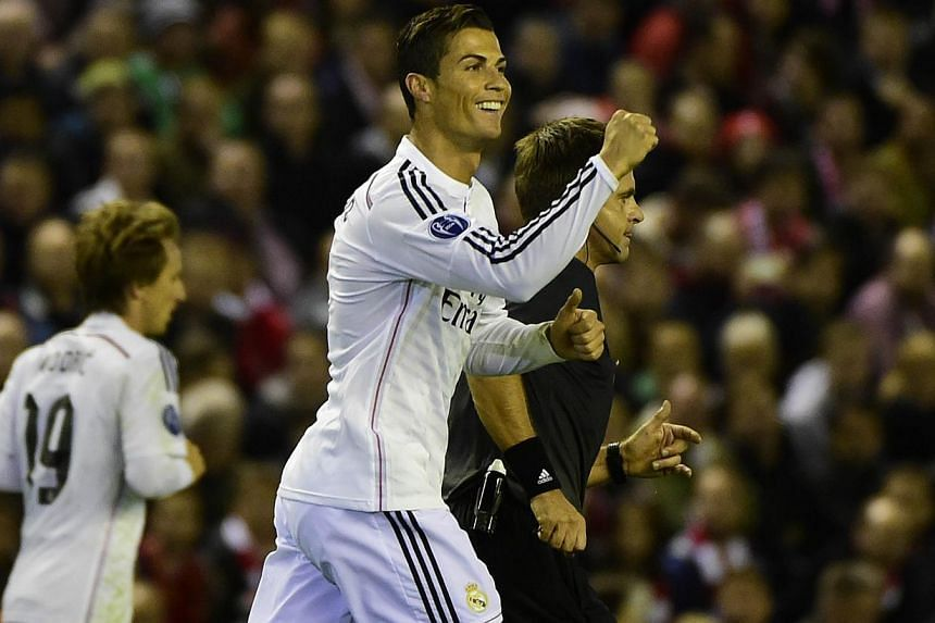 Real Madrid's Portuguese forward Cristiano Ronaldo celebrates scoring the opening goal during the Uefa Champions League, group B, football match between Liverpool and Real Madrid at Anfield in Liverpool, northwest England, on Oct 22, 2014. -- PHOTO: