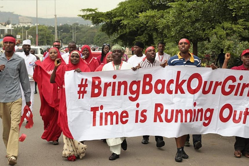 "Campaigners from ""#Bring Back Our Girls"" march during a rally calling for the release of the Abuja school girls who were abducted by Boko Haram militants, in Abuja on Oct 17, 2014. The Nigerian schoolgirls kidnapped by Boko Haram Islamists will"