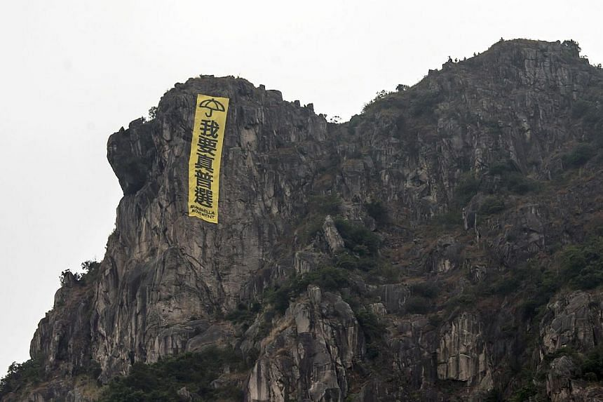 """A large banner hung by pro-democracy protesters is seen at Lion Rock, overlooking Kowloon in Hong Kong, on Oct 23, 2014. The yellow banner featured the slogan """"I want genuine universal suffrage"""" and an umbrella, the symbol adopted by democracy protes"""