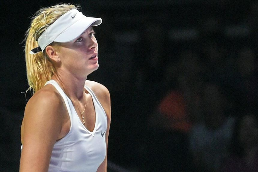Maria Sharapova of Russia reacts during a match against Petra Kvitova of Czech Republic at the Women's Tennis Association (WTA) finals round robin match in Singapore on Oct 23, 2014. -- PHOTO: AFP