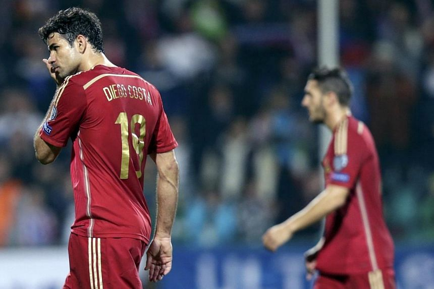 Diego Costa of Spain (left) leaves the pitch after their Euro 2016 qualification loss against Slovakia at the MSK stadium in Zilina Oct 9, 2014. -- PHOTO: REUTERS