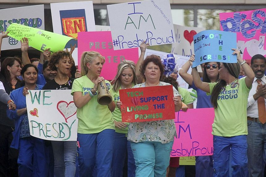 Nurses and health-care staff hold a rally in support of their colleagues Nina Pham and Amber Vinson, who contracted Ebola, outside the Texas Presbyterian Hospital in Dallas on Oct 17, 2014. Vinson no longer has the virus, her family said on Wednesday