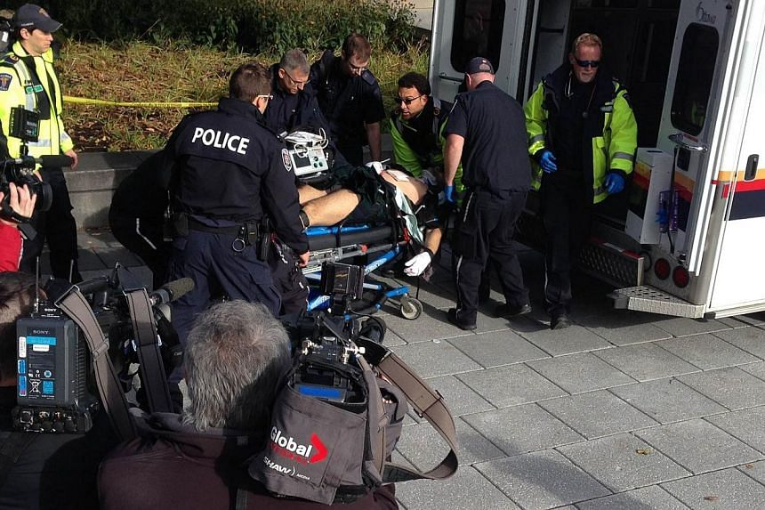 Police and medical personell moving a wounded Canadian soldier into an ambulance at the scene of a shooting at the National War Memorial in Ottawa, Canada on Oct 22, 2014. Singapore has condemned the shootings that took place at Canada's Na