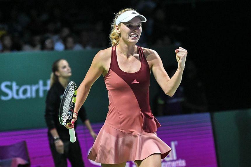 Caroline Wozniacki of Denmark reacts after defeating Agnieszka Radwanska of Poland at the Women's Tennis Association (WTA) finals round robin match in Singapore on Oct 23, 2014. -- PHOTO: AFP
