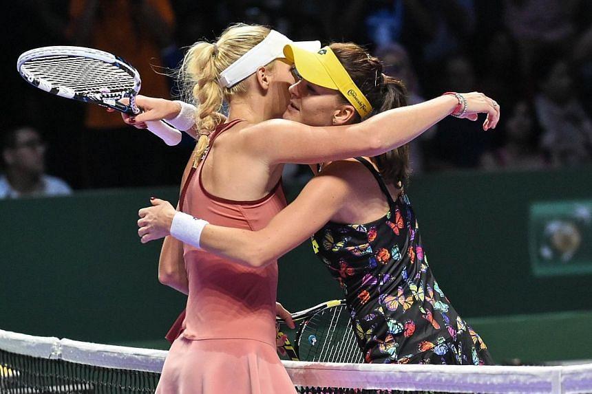 Caroline Wozniacki of Denmark (left) hugs defeated Agnieszka Radwanska of Poland at the Women's Tennis Association (WTA) finals round robin match in Singaporeon Oct 23, 2014. -- PHOTO: AFP