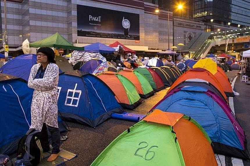 An Occupy Central protester reacts outside her tent before sunrise on a main road leading to the financial Central district in Hong Kong on Oct 16, 2014. -- PHOTO: REUTERS