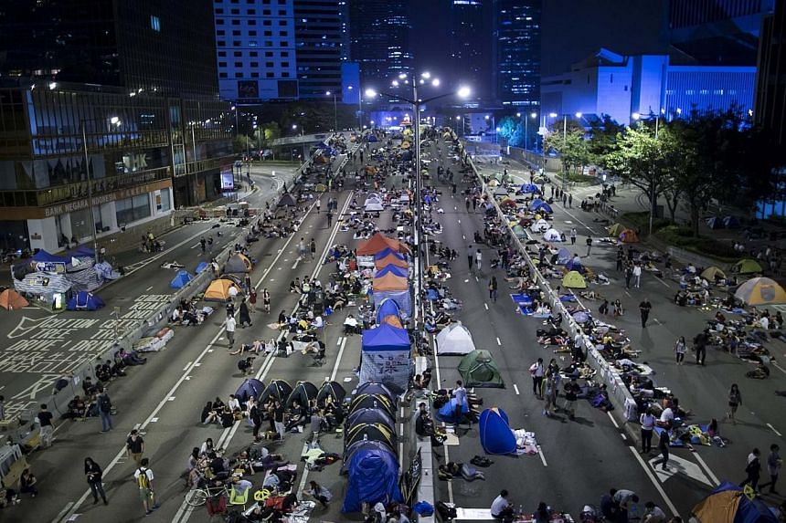 Protesters of the Occupy Central movement sleep in tents as pro-democracy protesters continue blocking areas around the government headquarters building in Hong Kong on Oct 11, 2014. -- PHOTO: REUTERS
