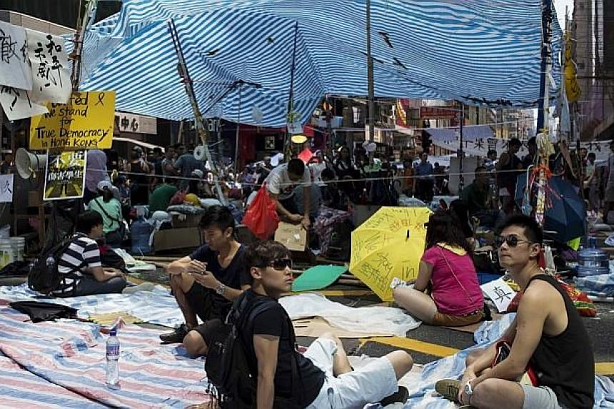 Protesters of the Occupy Central movement sit on a main road at the Mong Kok shopping district in Hong Kong on Oct 6, 2014. -- PHOTO: REUTERS