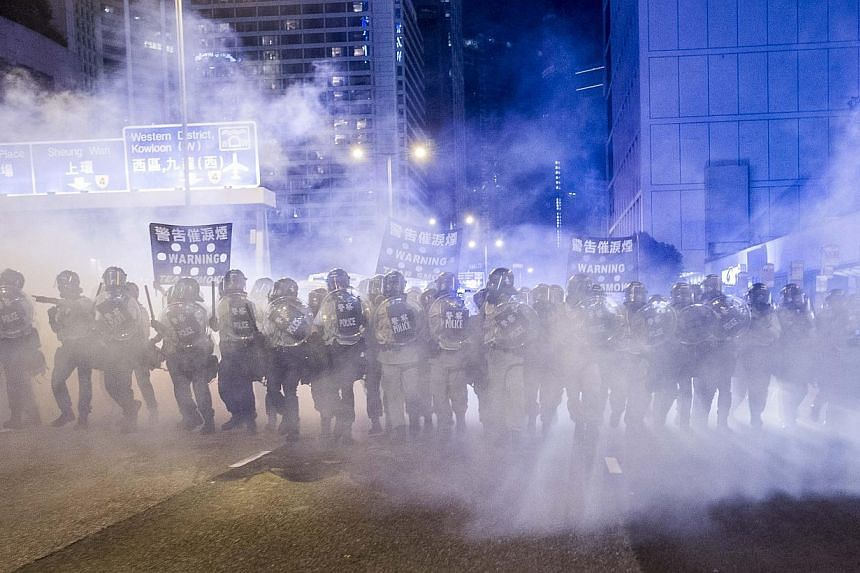 Police officers stand in a cloud of tear gas during a demonstration in Hong Kong on Sept 28, 2014. Britain said on Oct 22 it was likely to consider whether it needed to block British firms exporting tear gas to Hong Kong after police there used it ag