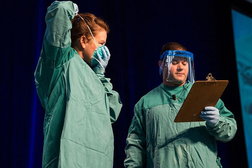 Barbara Smith (left), a nurse with Mount Sinai Health System, and Bryan Christensen, a doctor and member of the Center for Disease Control's Domestic Infection Control Team for the Ebola Response, demonstrate to health care professionals how to prope
