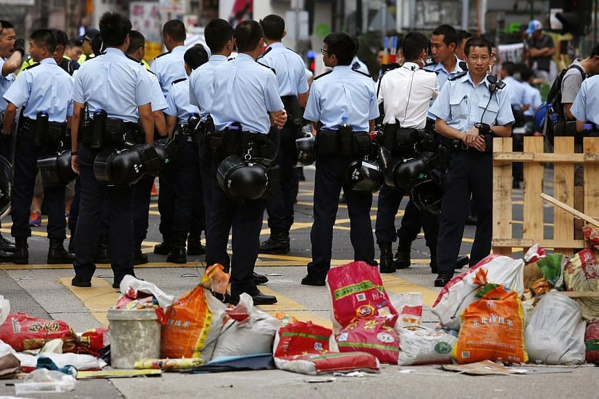 Police officers patrol in front of a barricade set up by pro-democracy protesters, and was partly demolished by anti-Occupy protesters, at Mongkok shopping district in Hong Kong, on Oct 22, 2014. -- PHOTO: REUTERS
