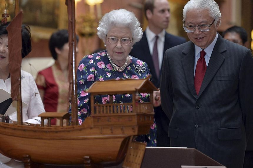 Britain's Queen Elizabeth and Singapore's President Tony Tan view a display of Singaporean items from the Royal Collection at Buckingham Palace in London on Oct 21, 2014. -- PHOTO: REUTERS