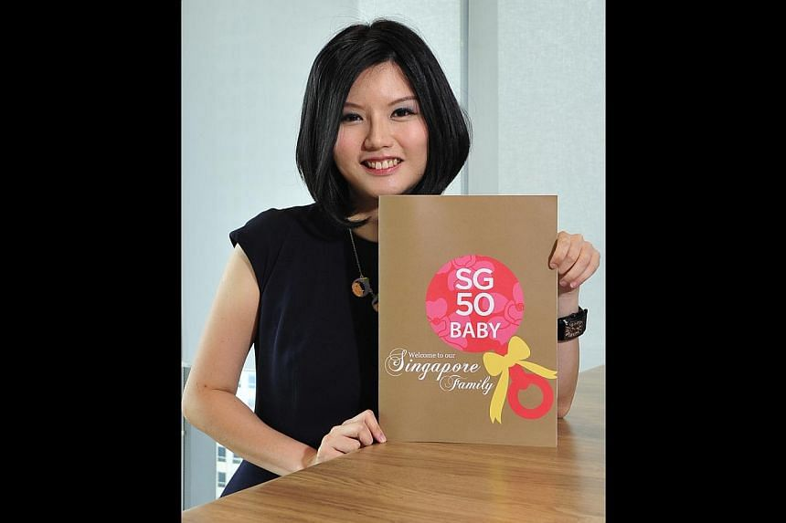 Ms Wang Shijia with the folder for the special birth certificate, both of which she designed for babies born next year, to commemorate Singapore's 50th year of independence.