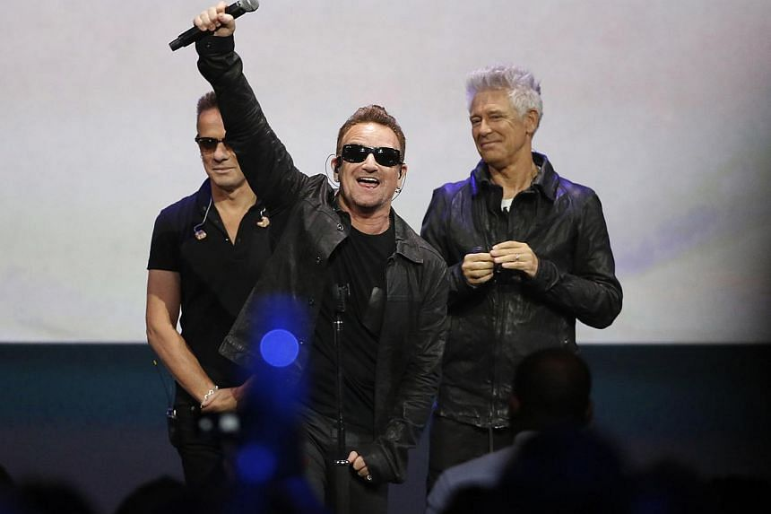 Bono (centre) of Irish rock band U2 gestures to the audience after performing at an Apple event at the Flint Center in Cupertino, California on Sept 9, 2014. -- PHOTO: REUTERS
