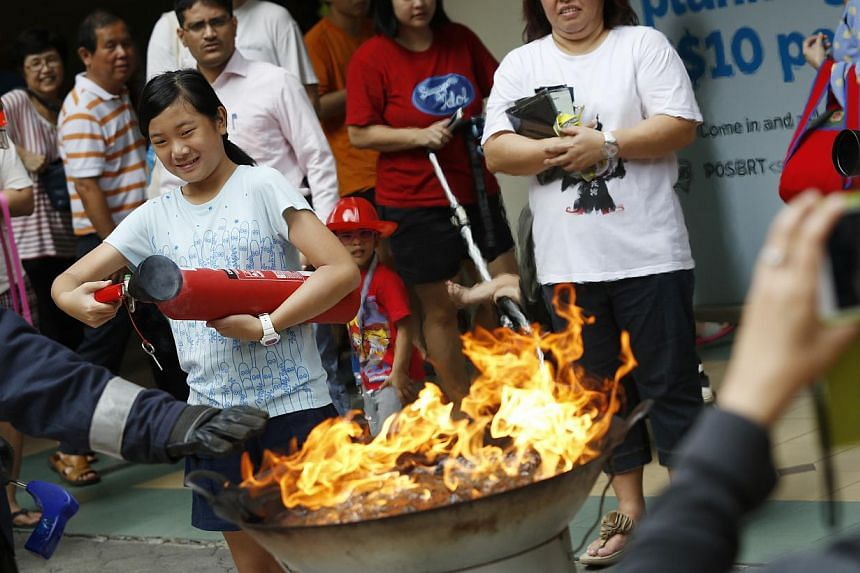 A girl attempts to put out a flaming wok with a fire extinguisher during a SCDF demonstration at the Tanjong Pagar Plaza on Oct 18, 2014. -- ST PHOTO:DESMOND LUI