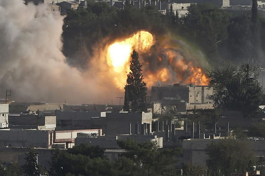 Smoke rises after an US-led air strike in the Syrian town of Kobani on Oct 10, 2014.