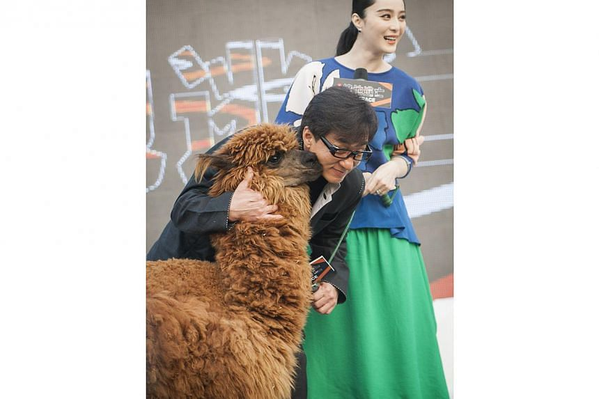Jackie Chan attends a press conference for his movie Skiptrace in Beijing on Oct 23, 2014 with Fan Bingbing and an alpaca. -- PHOTO: XINHUA