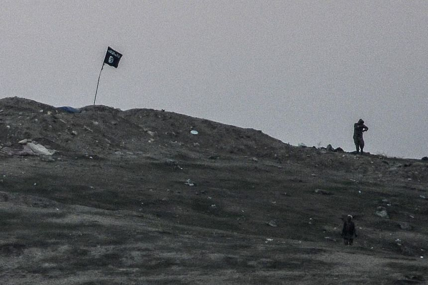 Militants of Islamic State (IS) stand near their flag on Tilsehir hill near Turkish border on Oct 23, 2014, at Yumurtalik village, in Sanliurfa province. -- PHOTO: AFP
