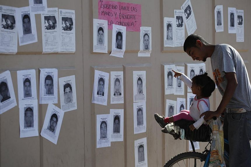 A girl points at photographs of missing students from the Ayotzinapa teachers' training college, attached to a wall surrounding the General Attorney's Office in Ciudad Juarez, on Oct 23, 2014. -- PHOTO: REUTERS