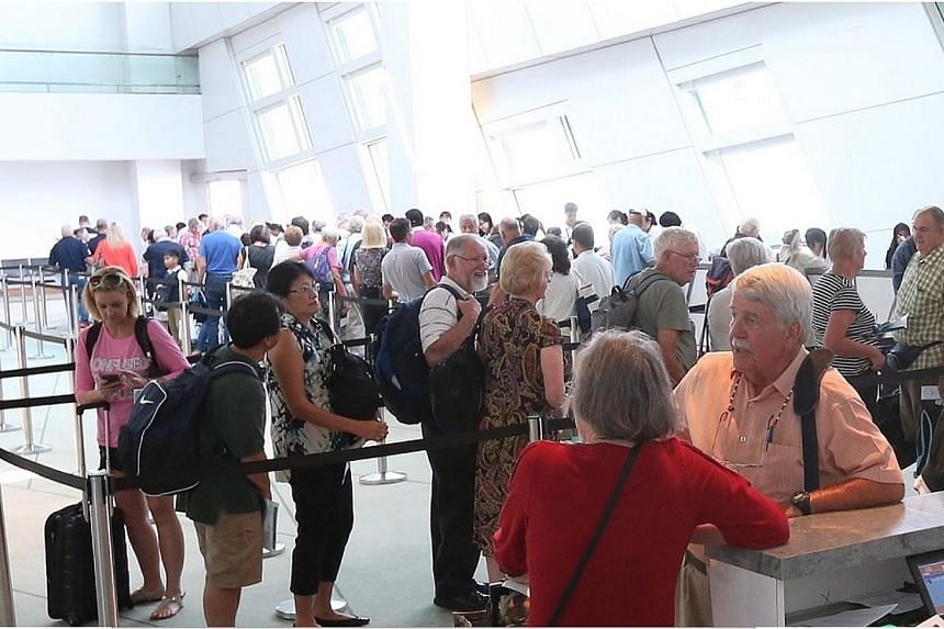 Passengers checking in at the Marina Bay Cruise Terminal on level 1.-- ST PHOTO: NEO XIAOBIN