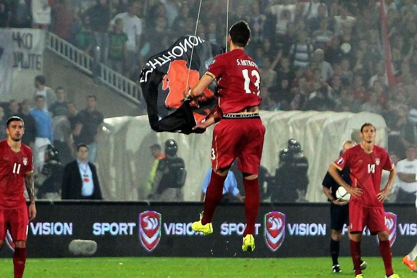 Serbia's defender Stefan Mitrovic grabs a flag with Albanian national symbols flown by a remotely operated drone during the UEFA Euro 2016 group I qualifying football match between Serbia and Albania in Belgrade on Oct 14, 2014.Albania's footba