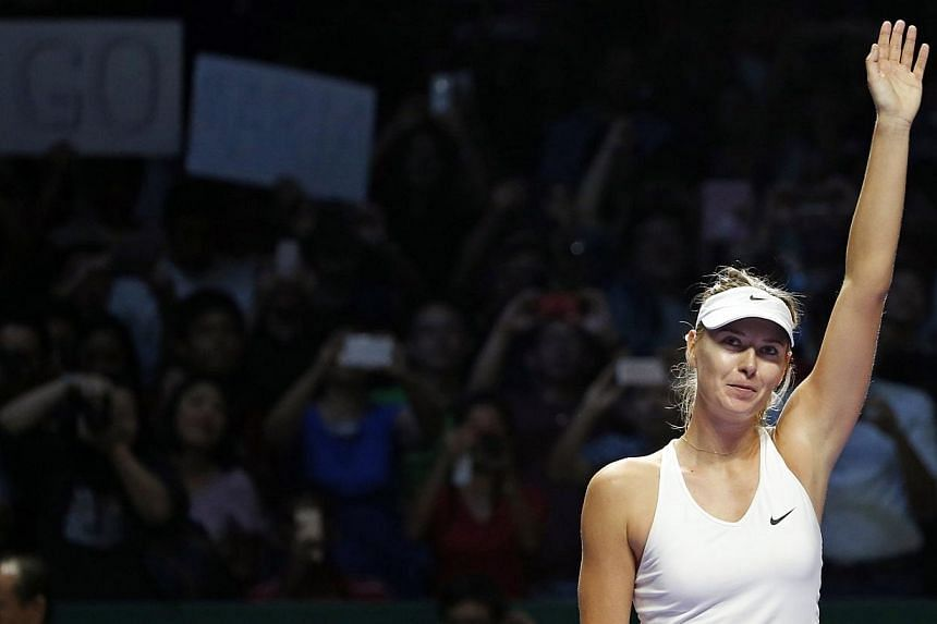 Maria Sharapova of Russia acknowledges the crowd after defeating Agnieszka Radwanska of Poland during their WTA Finals singles tennis match at the Singapore Indoor Stadium on Oct 24, 2014.Maria Sharapova recovered from a second-set meltdown to