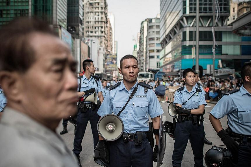 Hong Kong's police officers, regarded as among the cleanest and best paid in the world, are not used to being seen as public enemies. They are supposed to be the good guys but, overnight, they have become a subject of scorn. -- PHOTO: AGENCE FRANCE-P