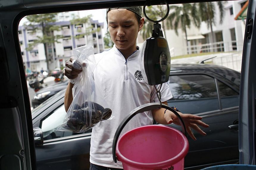 Ah Hua Kelong's Mr Wong Jing Kai weighing a batch of green mussels during his delivery run. The seafood is delivered within 12 hours of its harvest. Mr Terence Tee, 38, receiving his order from Ah Hua Kelong's business development manager, Mr Wong Ji