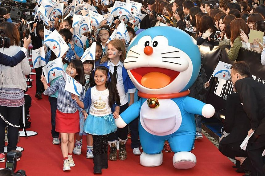 Japan's animation character Doraemon (centre) arrives with children on the red carpet for the 27th Tokyo International Film Festival opening ceremony in Tokyo on Oct 23, 2014. -- PHOTO: AFP