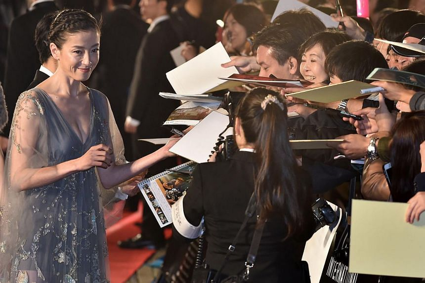 Japanese actress Rie Miyazawa (left), who performed in the film Pale Moon, is greeted by fans on the red carpet for the 27th Tokyo International Film Festival opening ceremony in Tokyo on Oct 23, 2014. -- PHOTO: AFP